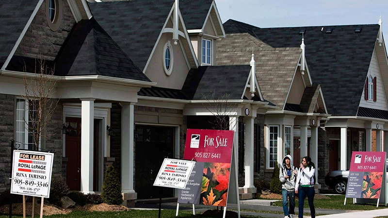 People walk past new homes that are for sale in Oakville, Ont., on Tuesday, April 14, 2009. (THE CANADIAN PRESS/Nathan Denette)