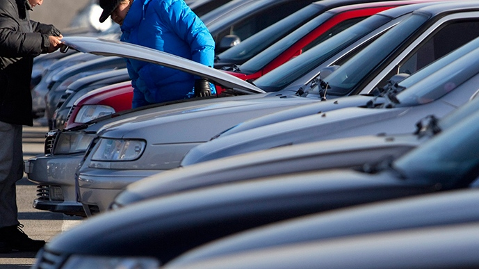 In this Dec. 23, 2010 file photo, customers open a car's engine hood to check interior parts. (AP Photo/Alexander F. Yuan, File)