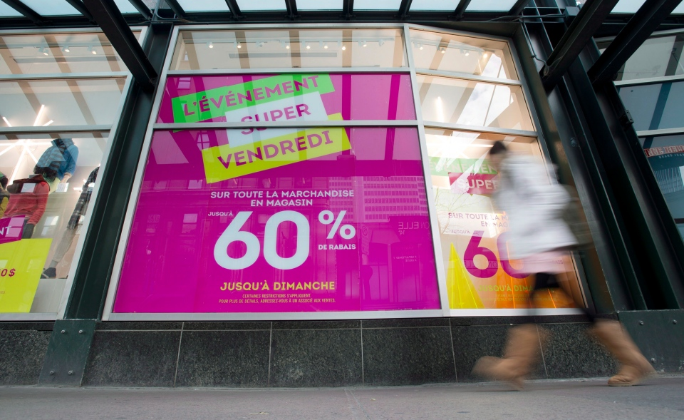 A woman walks by a store advertising additional discounts on 'Black Friday', in Montreal, Friday, November 23, 2012. (Graham Hughes / THE CANADIAN PRESS)