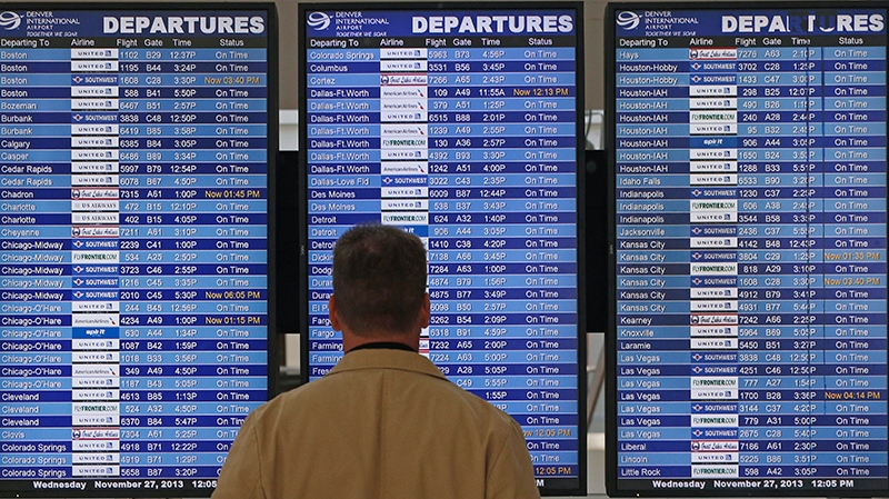 Checking the departures board at Denver International Airport, on Nov. 27, 2013. (Brennan Linsley / AP)