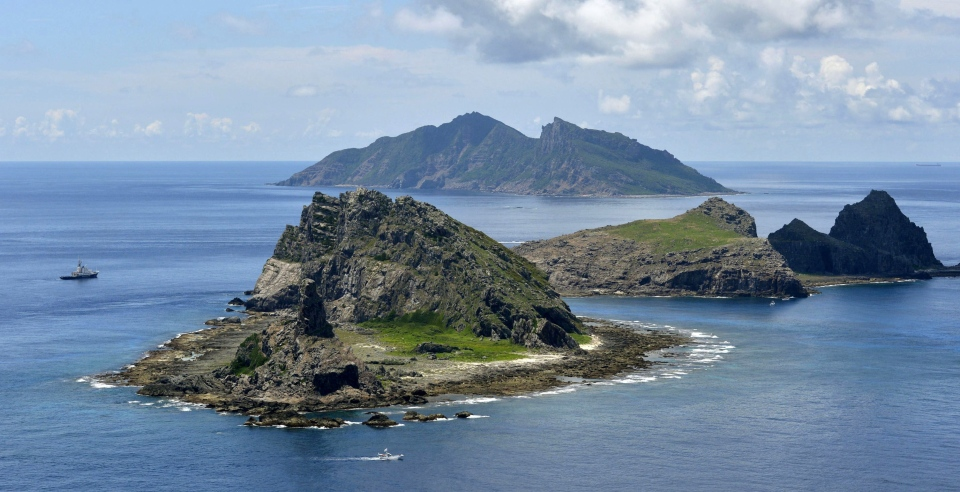 In this Sept. 2, 2012 file photo, the survey ship Koyo Maru, left, chartered by Tokyo city officials, sails around Minamikojima, foreground, Kitakojima, middle right, and Uotsuri, background, the tiny islands in the East China Sea, called Senkaku in Japanese and Diaoyu in Chinese. (AP Photo/Kyodo News, File)