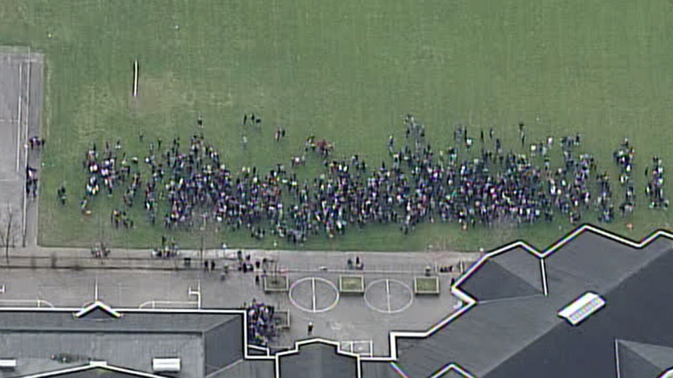 Students and staff fill a field near Gleneagle Secondary School in Coquitlam after a bomb threat forced an evacuation of the school Thursday, Nov. 28, 2013. (CTV)