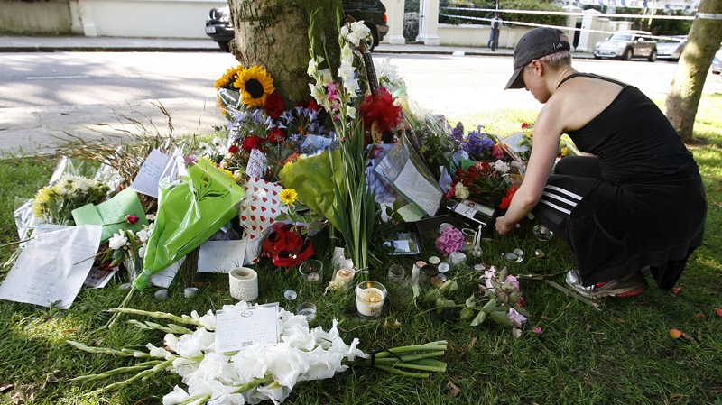 An unidentified woman leaves a floral tribute outside the residence of singer Amy Winehouse in Camden Square, north London, Sunday, July 24, 2011. (AP Photo/Akira Suemori)