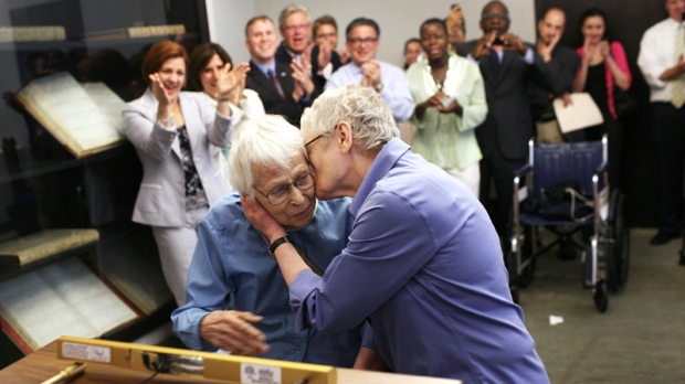 Phyllis Siegel, 77, right, kisses her wife Connie Kopelov, 85, after exchanging vows at the Manhattan City Clerk's office with New York City Council Speaker Christine C. Quinn in attendance, back left, on the first day New York State's Marriage Equality Act goes into effect, on Sunday, July 24, 2011. (AP / Michael Appleton)