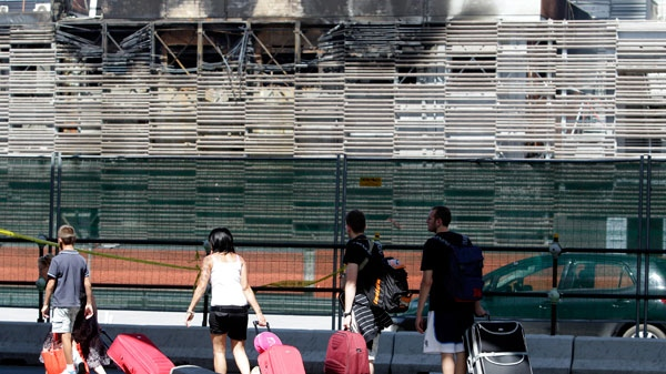 Tourists walk past the Tiburtina station, one of Rome's railway station, Sunday July 24, 2011. (AP / Pier Paolo Cito)
