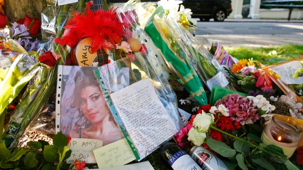 Floral tributes are seen outside the residence of singer Amy Winehouse in Camden Square, north London, Sunday, July 24, 2011. (AP / Akira Suemori)
