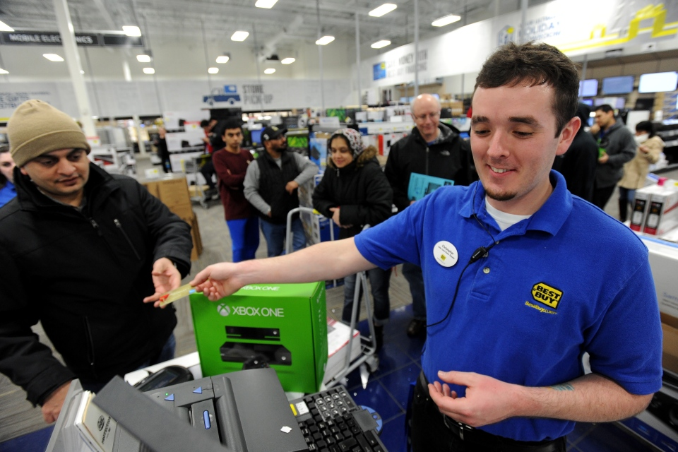 Best Buy employee Christopher Gervais, right, rings up an Xbox One game console on Black Friday early Nov. 29, 2013, in Dunwoody, Ga. All of the store's 120 employees were on hand to ring up items when the store opened for business on Thanksgiving Day. (AP Photo/David Tulis)