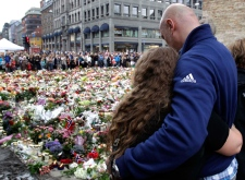 People embrace and mourn at the massive flower field laid in memory of victims of Friday's twin attacks in front of the Oslo Cathedral in Oslo, Norway, Monday, July 25, 2011. (AP / Frank Augstein)