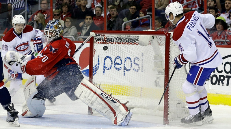Montreal Canadiens center Tomas Plekanec (14) scores a goal on Washington Capitals goalie Braden Holtby (70) as Canadiens center Daniel Briere (48) looks on nam iceduring the second period of an NHL hockey game in Washington, Friday, Nov. 29, 2013. (AP Photo/Carolyn Kaster)