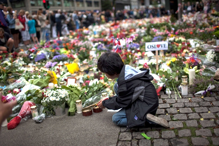 A boy lights a candle to pay tribute to victims of Friday's twin attacks in central Oslo, Norway, Monday, July 25, 2011. (AP / Emilio Morenatti)