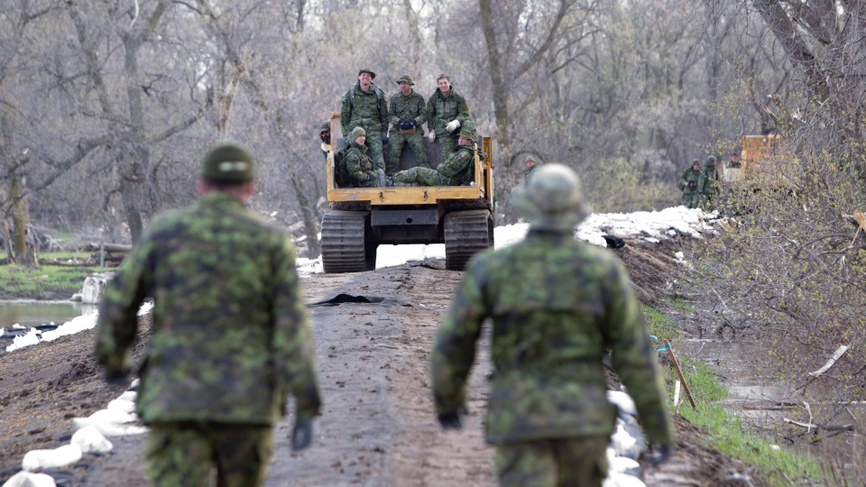Members of CFB Shilo are seen leaving the Portage Diversion Dike along the Assiniboine River after fixing weak areas with sandbags near Portage La Prairie, Man., Wednesday, May 11, 2011. (Jonathan Hayward / THE CANADIAN PRESS)