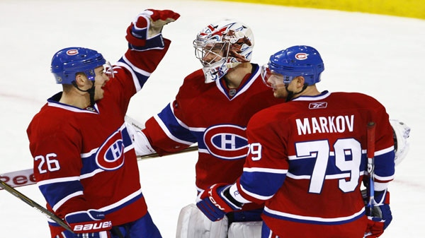 Montreal Canadiens goalie Carey Price is congratulated by teammates Josh Gorges, left, and Andrei Markov, from Russia, after shutting out the Vancouver Canucks 2-0 during NHL hockey action Tuesday, November 9, 2010 in Montreal. THE CANADIAN PRESS/Paul Chiasson