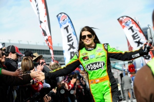 Danica Patrick reaches to greet fans as she walks onto the track during the introductions for the NASCAR Sprint Cup series auto race at Texas Motor Speedway in Fort Worth, Texas. Nov. 3, 2013 (AP Photo/Ralph Lauer, File)