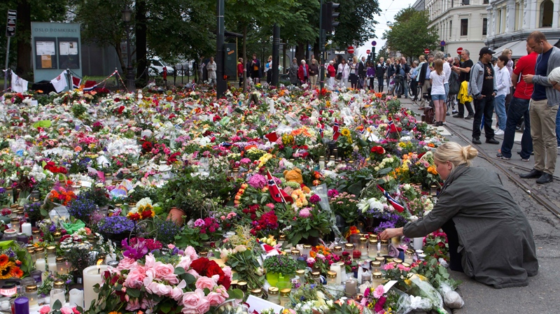A woman places flowers amongst candles and other floral tributes in memory of the victims of Friday's bomb blast and shooting massacre in Norway, in Oslo Monday July 25, 2011. (Scanpix Norway / Berit Roald)