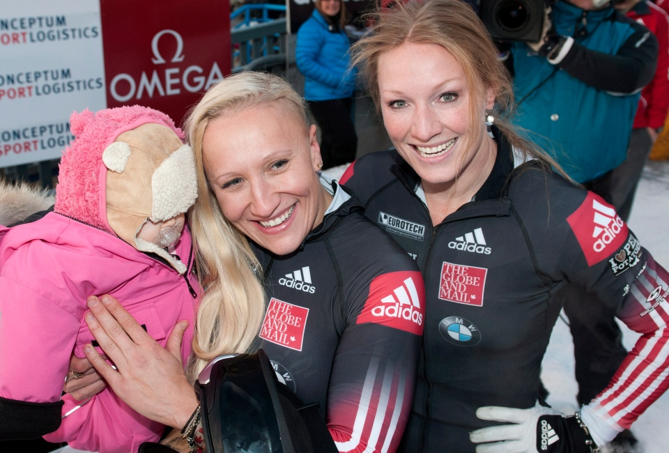 Canada's Kaillie Humphries, centre, and Heather Moyse celebrate with Kaillie's five-month-old niece Haze Lewis after winning the women's World Cup bobsled race in Calgary, Alta., Saturday, November 30, 2013. (Larry MacDougal / THE CANADIAN PRESS)