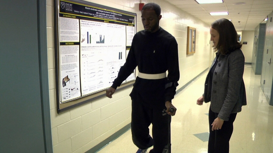 Spinal cord injury patient Christopher McClendon walks with a cane in Atlanta, Georgia.