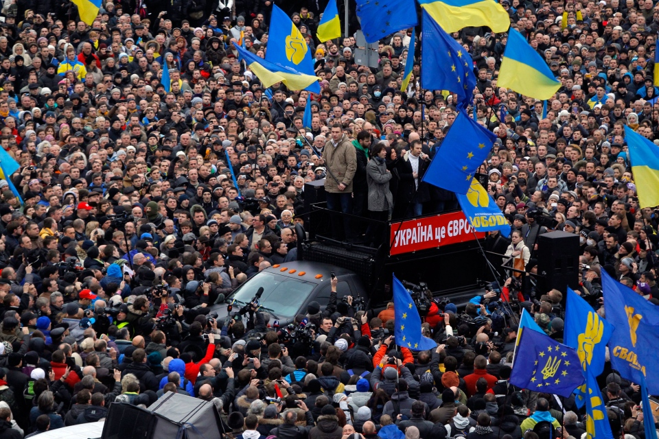 Lawmaker and chairman of the Ukrainian opposition party Udar (Punch), WBC heavyweight boxing champion Vitali Klitschko, left on the platform, waves a flag during a rally in downtown Kiev, Ukraine, on Sunday, Dec. 1, 2013. (AP / Sergei Grits)