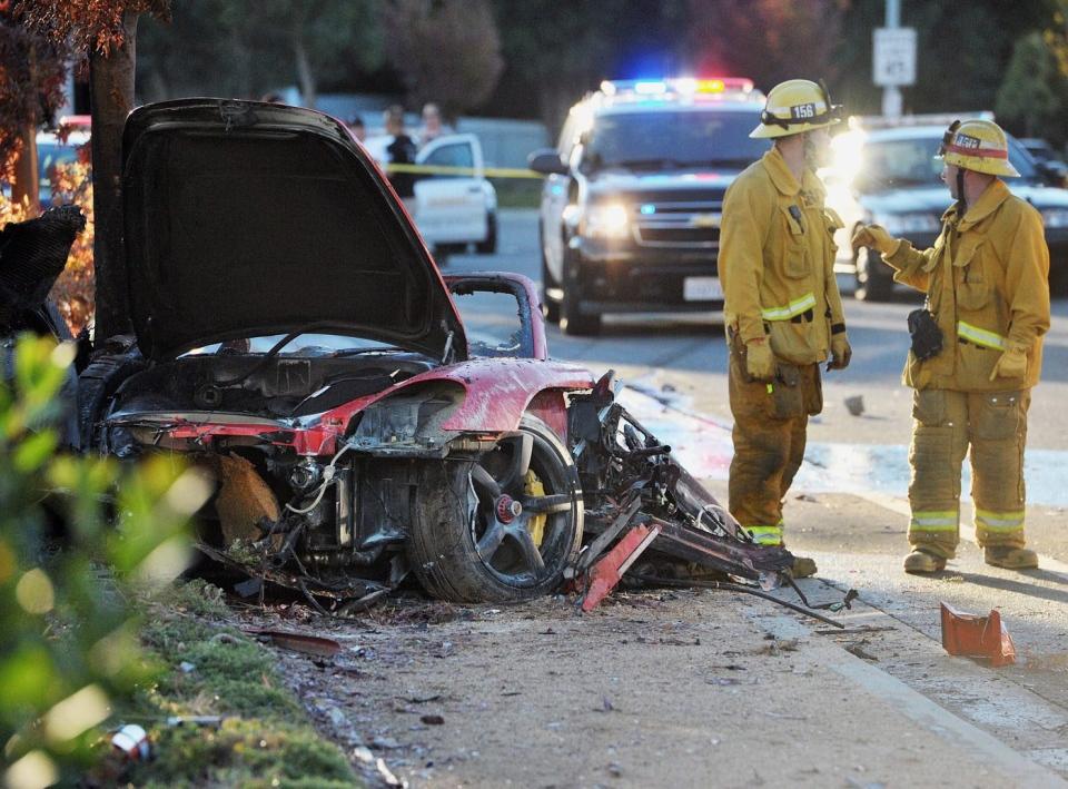 Sheriff's deputies work near the wreckage of a Porsche that crashed into a light pole on Hercules Street near Kelly Johnson Parkway in Valencia, Calif., on Nov. 30, 2013.  (The Santa Clarita Valley Signal, Dan Watson)