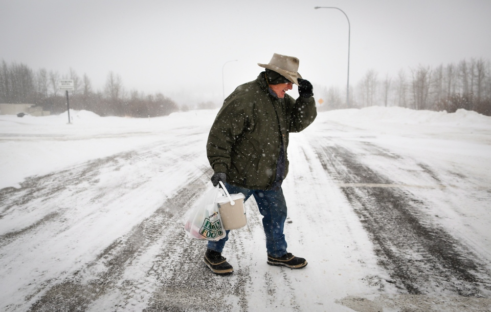 Joe Doiran holds his hat on as he crosses a road during a blizzard in Cremona, Alta., Monday, Dec. 2, 2013. (Jeff McIntosh / THE CANADIAN PRESS)