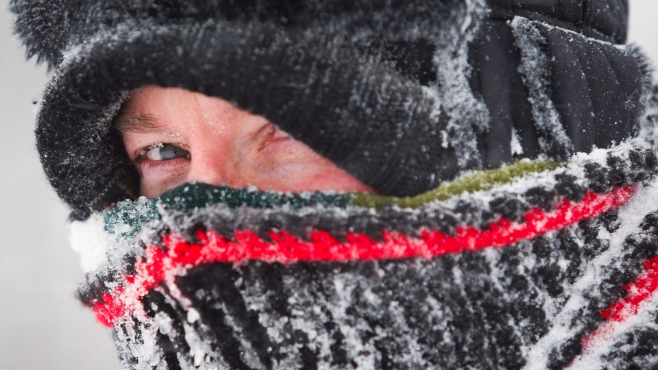 David Reid peers out from his wrappings as he uses a snow blower to clear his driveway during a blizzard near Cremona, Alta., Monday, Dec. 2, 2013. (Jeff McIntosh / THE CANADIAN PRESS)