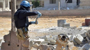 A member of UN investigation team takes samples of sands near a part of a missile is likely to be one of the chemical rockets according to activists, in Damascus countryside of Ain Terma, Syria, Wednesday, Aug. 28, 2013. (United Media Office of Arbeen)