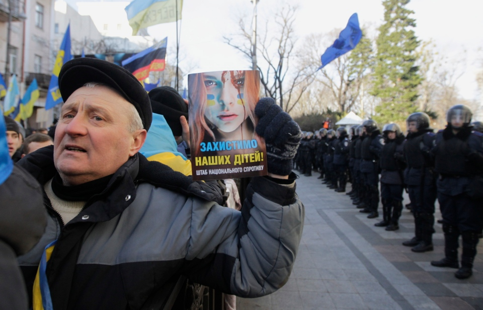 A protester holds a leaflet reading 'Let's protect our children' as he and others rally outside the Parliament in Kyiv, Ukraine, on Tuesday, Dec. 3, 2013. (AP / Sergei Chuzavkov)