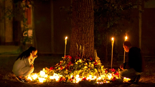 Candles burn as people look at tributes outside the Oslo Cathedral in Oslo, in memory of the victims of Friday's bomb attack and shooting rampage, in the early hours of Tuesday, July 26, 2011. (AP / Matt Dunham)