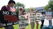Protestors opposed to the Keystone XL pipeline hold signs outside the office of Rep. Lee Terry, R-Neb., in Omaha, Neb., Tuesday, July 26, 2011. (AP / Nati Harnik)