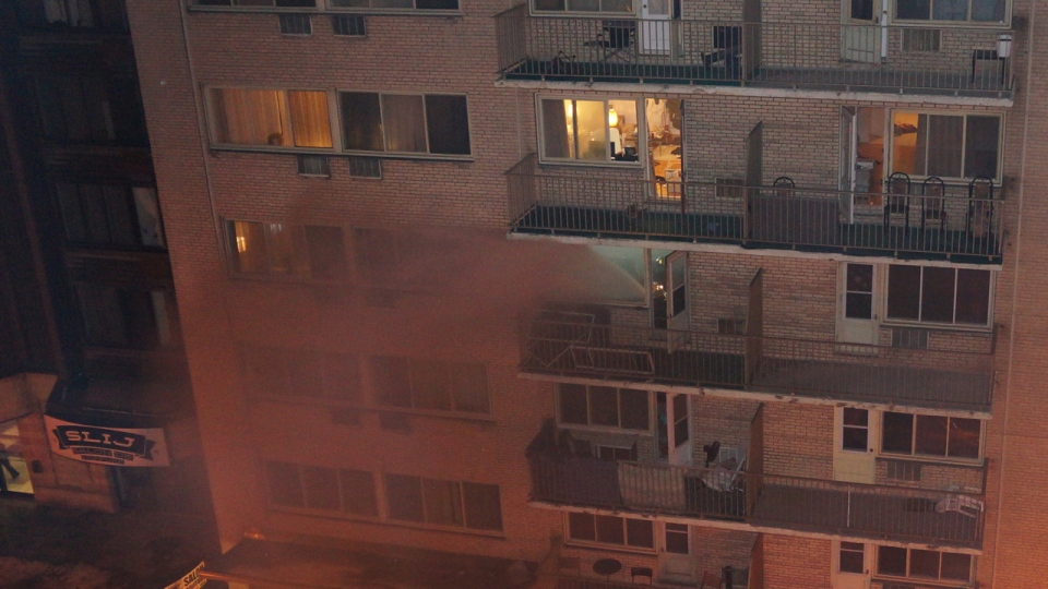 Smoke pours from a fourth floor apartment