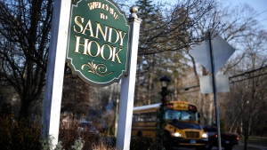 A bus drives past a sign reading Welcome to Sandy Hook in Newtown, Conn. on Wednesday, Dec. 4, 2013. (AP / Jessica Hill)
