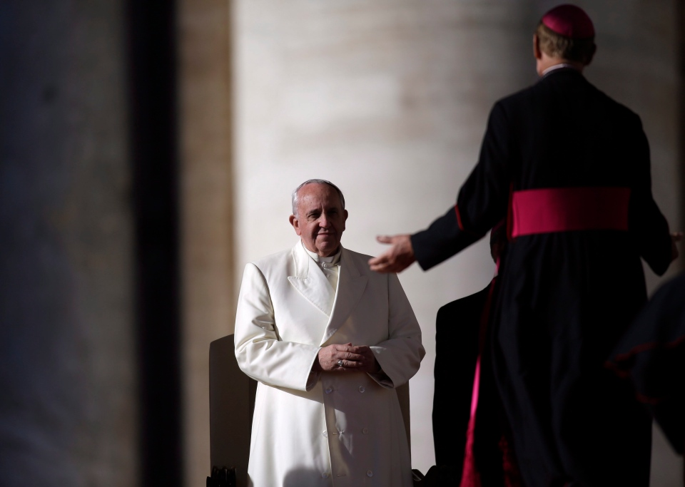 Pope Francis is greeted by a bishop in St. Peter's Square during the weekly general audience at the Vatican, Wednesday, Dec. 4, 2013. (AP Photo/Gregorio Borgia)