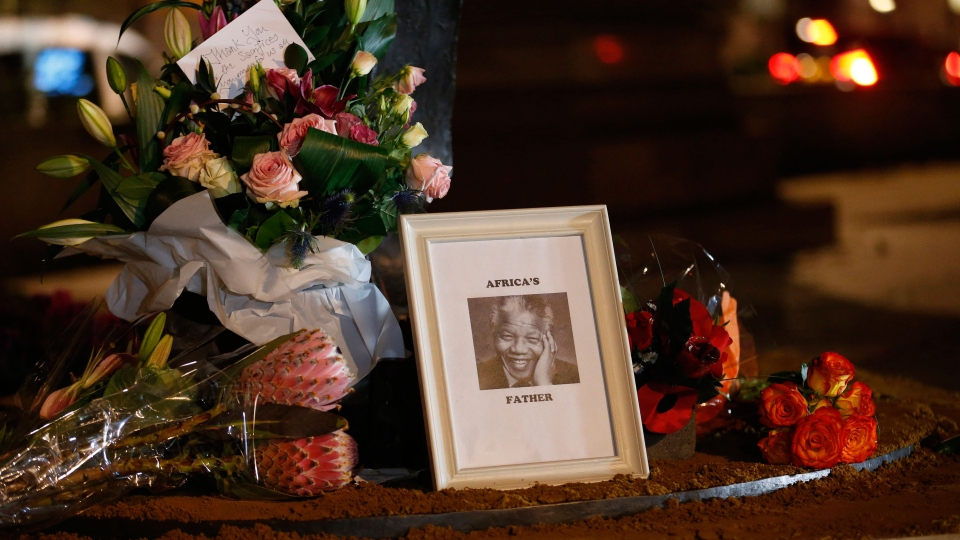 Floral tributes and a picture are left at a statue of Nelson Mandela at Parliament Square in London, Friday, Dec. 6, 2013. (AP / Sang Tan)