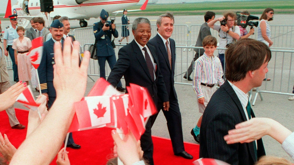 Nelson Mandela walks with then-prime minister Brian Mulroney  on his arrival in Ottawa for a three-day visit to Canada, on June 17, 1990. (Chuck Mitchell / THE CANADIAN PRESS)