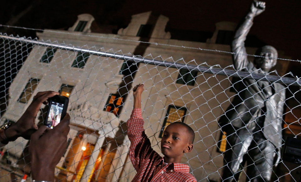 Keaton Anderson, 10, poses for a photograph for his father Dijon Anderson, of Bowie, Md., as they visit the statue of Nelson Mandela at the South African Embassy in Washington, which is currently under renovation, Thursday, Dec. 5, 2013. (AP / Charles Dharapak)