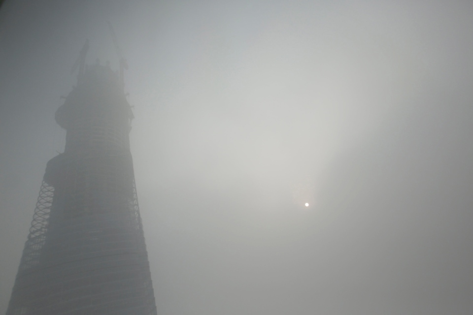 A building under construction is covered with haze in Shanghai, China, Friday, Dec. 6, 2013. S(AP Photo/Eugene Hoshiko)