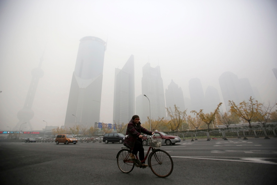 A woman rides covered with heavy haze in Shanghai, China, Friday, Dec. 6, 2013. (AP Photo/Eugene Hoshiko)