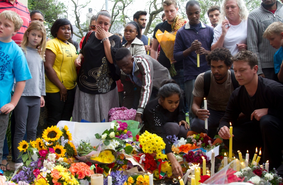 Mourners lay floral and candle tributes to former South African president Nelson Mandela outside his Johannesburg home, Friday, Dec. 6, 2013. (AP / Athol Moralee)
