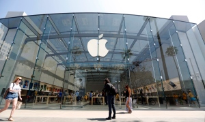 In this Thursday, May 9, 2013 photo, people walk near the Apple store in Santa Monica, Calif.  (AP Photo/Reed Saxon)