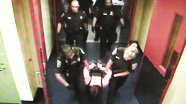 Ottawa police hold Roxanne Carr in this image taken from a 2008 video. A cellblock video has been released that captures the arrest of a woman who claims Ottawa police injured and strip-searched her before leaving her naked in a cell without medical attention.