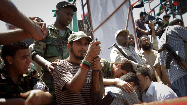 Libyans react near the coffin of Libyan rebels' slain military chief Abdel-Fattah Younis in the rebel-held town of Benghazi, Libya, Friday, July 29, 2011. (AP / Sergey Ponomarev)
