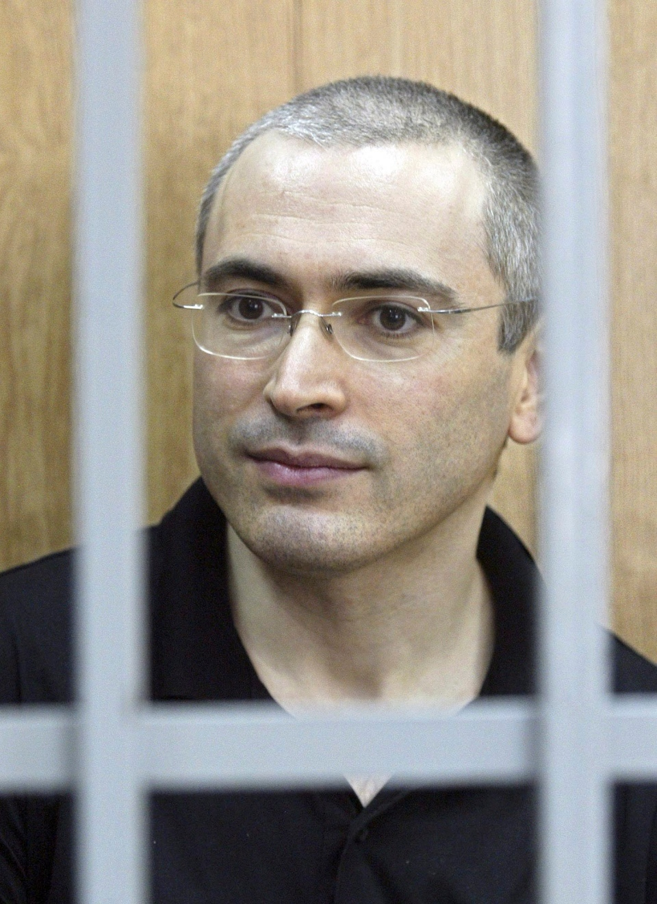 Former Yukos CEO Mikhail Khodorkovsky sits in a courtroom behind bars in Moscow, Russia, Friday, July 30, 2004. (AP / Sergey Ponomarev)