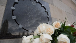 Flowers sit next to a plaque at the Ecole Polytechnique in Montreal, Friday, Dec. 6, 2013, in memory of the 14 women who died at the hands of a gunman at the university Dec. 6, 1989. (Graham Hughes / THE CANADIAN PRESS)