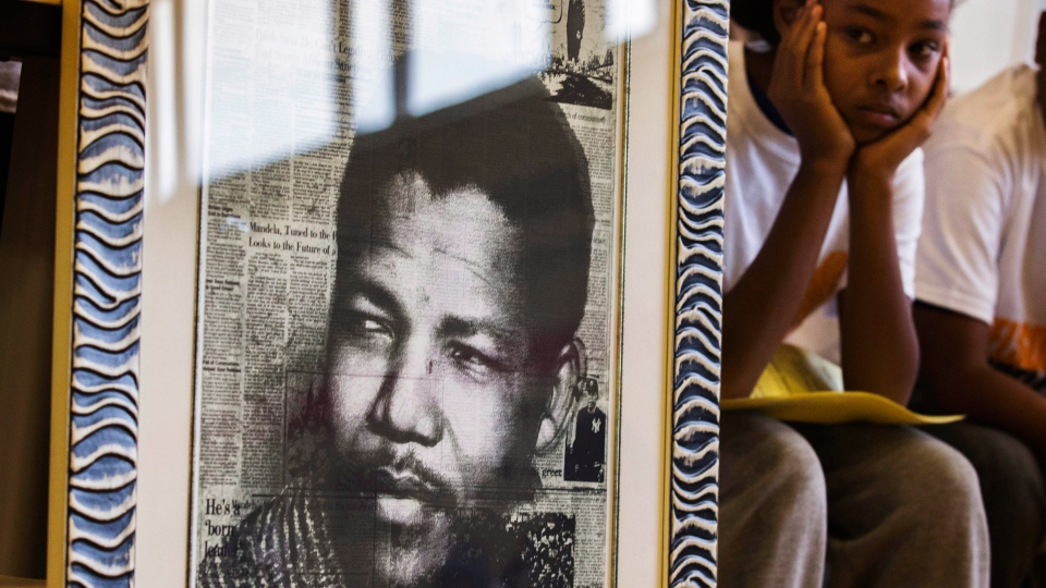 A young woman sits behind a picture of the late former president of South Africa Nelson Mandela during a celebration of his life at the Nelson Mandela Park Public School in Toronto, Friday, Dec. 6, 2013. (Mark Blinch / THE CANADIAN PRESS)