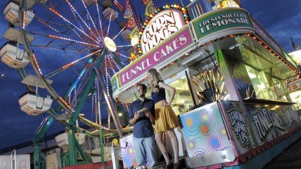 Luke Gunn, left, and Jacqueline Allee, right, both of Pueblo, have their picture taken on the midway for an engagement photo session at the Denver County Fair in Denver on Thursday, July 28, 2011. (AP Photo/Chris Schneider)