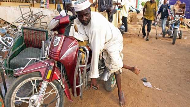 In this Thursday, May 13, 2010 photo, a man suffering from polio leans against a make shift motor bike in Kano, Nigeria. (AP Photo/Sunday Alamba)