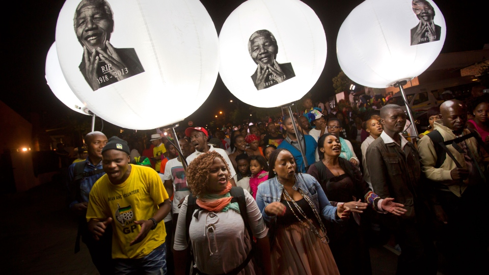 Mourners holding illuminated balloons showing the face of Nelson Mandela march and sing to celebrate his life, on the street outside his old house in Soweto, Johannesburg, South Africa, Saturday, Dec. 7, 2013. (AP / Ben Curtis)