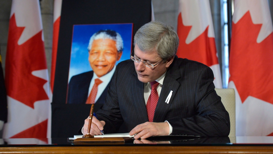 Prime Minister Stephen Harper pens a message in the Book of Condolences after the passing of Nelson Mandela, in the House of Commons in Ottawa, Friday Dec. 6, 2013. (Adrian Wyld / THE CANADIAN PRESS)