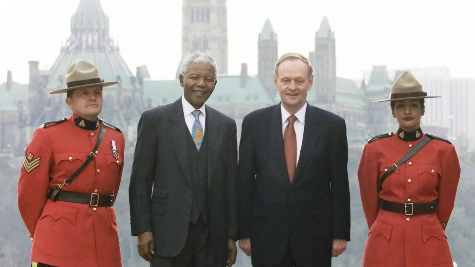 Former South African president Nelson Mandela and then-prime minister Jean Chretien are flanked by RCMP constables in Hull, Quebec, as they pose for photographs across the river from the Parliament Buildings on Monday, Nov. 19, 2001. (Fred Chartrand / THE CANADIAN PRESS)