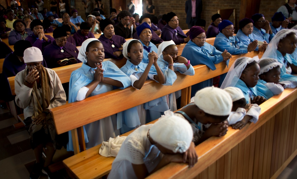 Young members of the choir pray at a morning mass in memory of Nelson Mandela at the Regina Mundi church, which became one of the focal points of the anti-apartheid struggle, in Soweto, Johannesburg, South Africa Sunday, Dec. 8, 2013. (AP / Ben Curtis)