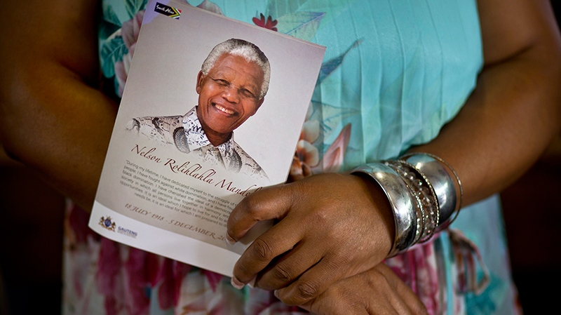 A mourner holds a booklet showing Nelson Mandela at a morning mass in his memory at the Regina Mundi church in Soweto, Johannesburg, South Africa Sunday, Dec. 8, 2013. (AP / Ben Curtis)